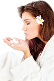 Woman smelling flower. Pretty woman in bathrobe  smelling flower, isolated on white Stock Photo