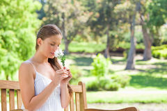 Woman smelling a flower while sitting on a park bench Stock Images