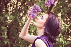 Woman smelling flower on tree branch Royalty Free Stock Photography