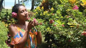 Woman smelling a flower stock footage