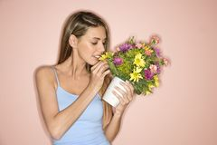 A woman smelling flowers. Stock Image