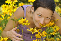 Woman smelling flowers. Royalty Free Stock Photography