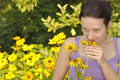 Woman smelling flowers. Stock Photography