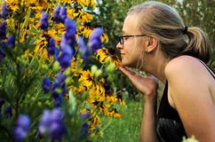 Woman smelling flowers. In the garden Royalty Free Stock Photo