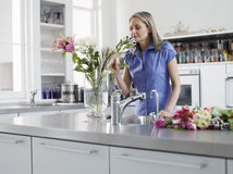 Woman Smelling Flowers In Kitchen Royalty Free Stock Photos