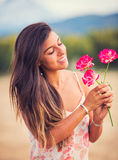 Woman smelling flowers in nature Stock Photography