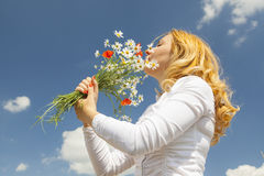 Woman smelling flowers Stock Photos