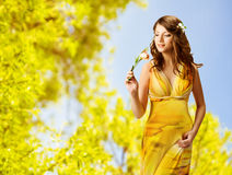 woman smelling flowers, spring portrait of beautiful girl in yellow dress
