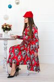 Woman smelling flowers. The girl with long hair. girl in a red hat sitting at a table and smelling flowers in a vase Stock Photography