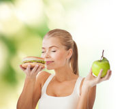 Woman smelling hamburger and holding apple Stock Image