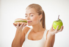Woman smelling hamburger and holding apple. Healthy woman smelling hamburger and holding apple Royalty Free Stock Photo