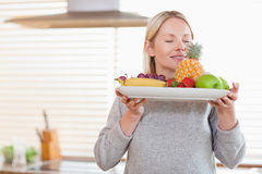 Woman smelling on her fruit plate Stock Photo