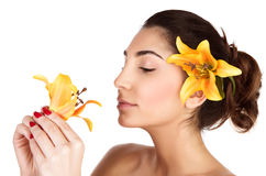 Woman smelling lily flower. Image of beautiful arabic woman with yellow lily flower in head enjoying her smell, cute brunette girl with closed eyes isolated on Royalty Free Stock Image