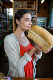 Woman smelling a loaf of bread Royalty Free Stock Photos