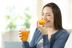 Woman smelling an orange and holding a juice. Happy woman smelling an orange and holding a juice sitting on a couch in the living room at home Stock Images