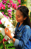Woman smelling orchid flowers royalty free stock photo