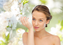 Woman smelling perfume from wrist of her hand Stock Images