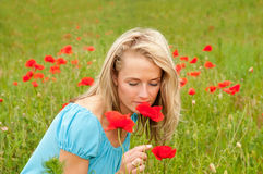 Woman smelling a poppy Stock Photos