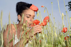 Woman smelling poppy Royalty Free Stock Photos