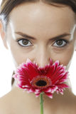 Woman smelling a red flower Stock Photography