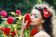 Woman smelling red roses Stock Images