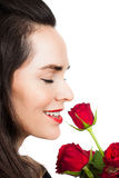 Woman smelling a rose. Close-up portrait of a beautiful woman smiling and smelling a rose. Isolated on white royalty free stock photos
