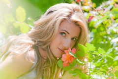 Woman smelling a rose in the garden Royalty Free Stock Photo