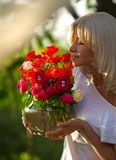 Woman smelling at roses. Enjoying the scent stock photography