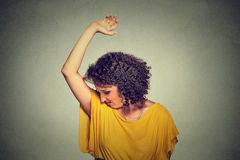 Woman, smelling, sniffing her wet armpit, something stinks, very bad foul odor. Closeup portrait young woman, smelling, sniffing her wet armpit, something stinks Stock Photos