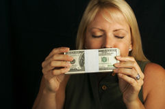 Woman Smelling Stack of Money Stock Images