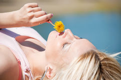Woman smelling yellow dandelion Royalty Free Stock Photos