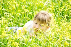 Woman smelling yellow flowers. Young woman lying on the grass and smelling yellow flowers Stock Photo