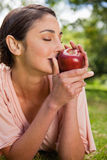 Woman smells an apple while lying in grass Royalty Free Stock Photos