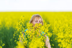 The woman smells aromas of spring flowers. The woman smells aromas of spring flowers on colza the field Royalty Free Stock Image
