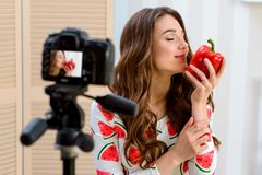 Woman smells a bell pepper. Food blogger holding a red vegetable and recording a new video issue for her blog using camera on tripod stock photos
