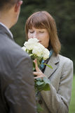 Woman smells on flowers Royalty Free Stock Photography