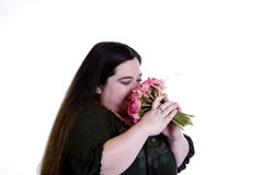 Woman smells Flowers. A woman smells a bouquet of flowers stock photography