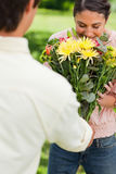 Woman smells flowers with are being given to her by a friend Stock Photography