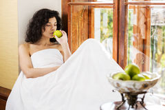 Woman smells green apple on wooden sill Royalty Free Stock Image