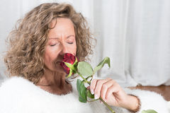Woman smells rose. Sitting on couch Royalty Free Stock Photography
