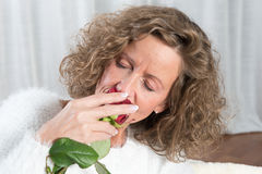 Woman smells rose. Sitting on couch Stock Image