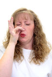 Woman smells something really bad. Caucasian woman smells something really bad and is pinching her nose in disgust.  Isolated on white Stock Photography