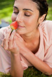 Woman smells an strawberry while lying in grass Royalty Free Stock Photography