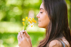 Woman smells yellow florets. Young beautiful smiling woman smells small bouquet of yellow florets, against green summer garden Royalty Free Stock Photos