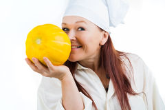 The woman smells a yellow melon Stock Photos