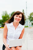 Woman with a smile. Work with a netbook raises a smile Stock Photo