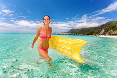 Woman smile beach raft. Woman smiling with yellow inflatable raft in turquoise waters near beach resort on vacation Stock Images