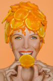 Woman with smile eats  slice of orange Royalty Free Stock Images
