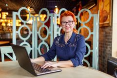 Woman with a smile in glasses looks directly and works behind a laptop at a table in a cafe. A woman in age, in a blue dress, redhead with a smile in glasses Royalty Free Stock Image