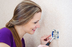Woman with a smile makes repairs electrical outlet Stock Images